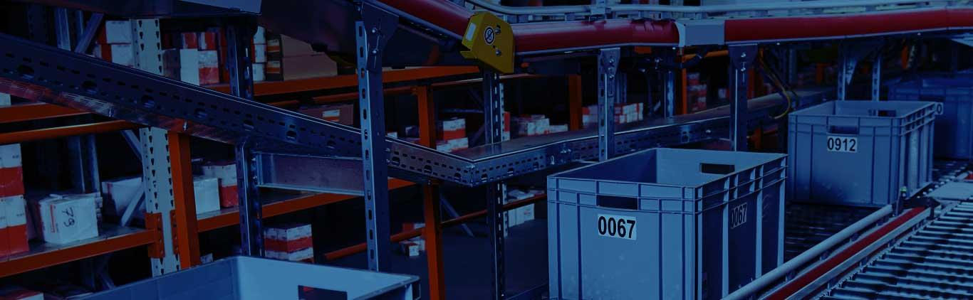 Warehouse product bins moving down a conveyor belt.