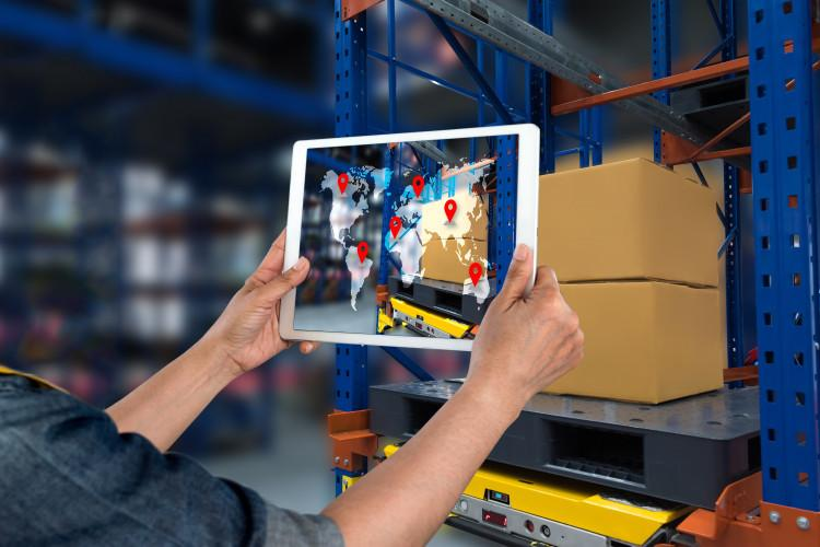 Warehouse worker holding up tablet with a picture of the world and map points on it