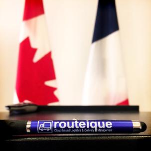 Routeique pen in front of the Canadian and French flags.