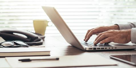 Person sitting at a desk typing on a laptop.