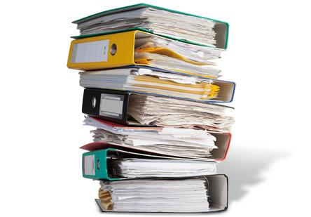 Stack of six binders full of paper.