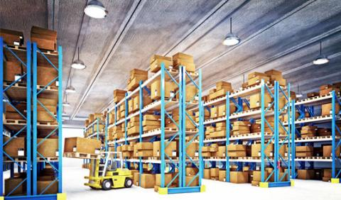 Wide shot of a warehouse with a yellow forklift pulling something off a high shelf.