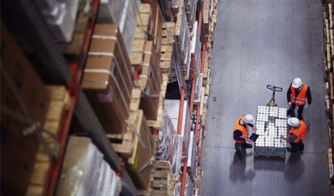 Birds eye view of warehouse workers in a warehouse loading stock onto a pallet jack.