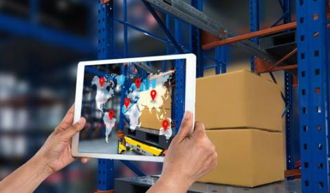 Routeique's order portal system shown on a tablet being held up by two hands in a warehouse