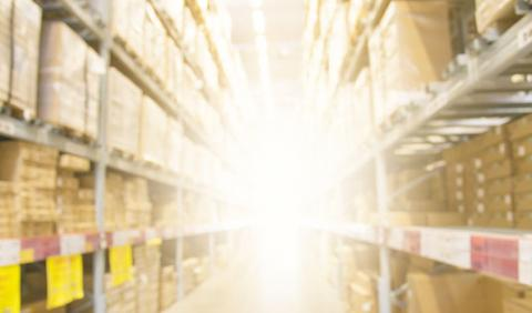 Aisle in a warehouse with a bright light shining at the far end.