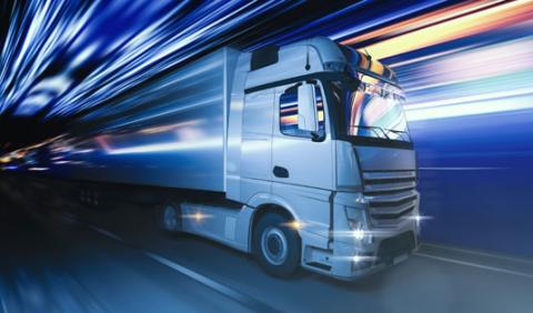 Semi truck travelling fast down a road.