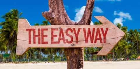 "Wood arrow sign pointing to the right with the words ""The Easy Way""."