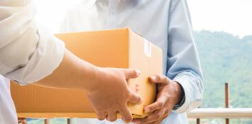 One person handing a box to another person, showing concept of product/vendor management